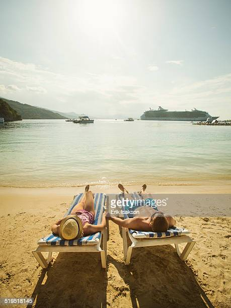 Caucasian couple holding hands in deck chairs on beach