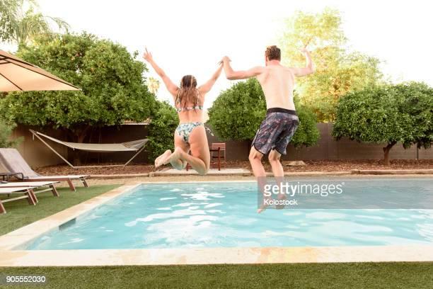caucasian couple holding hands jumping into swimming pool - piscina pubblica all'aperto foto e immagini stock