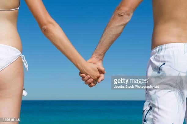 caucasian couple holding hands on beach - parte do meio - fotografias e filmes do acervo