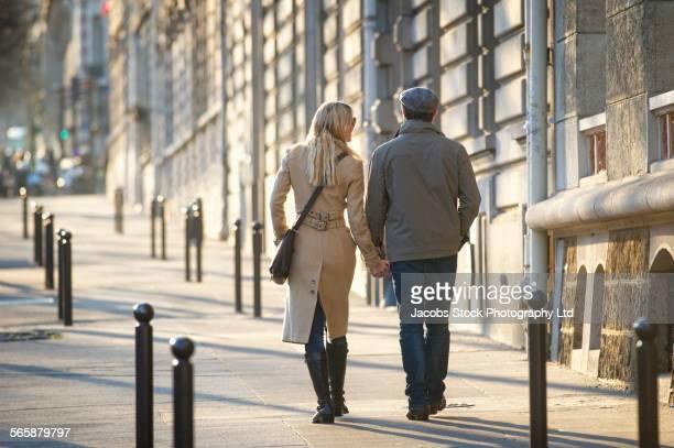 Caucasian couple holding hands on city sidewalk