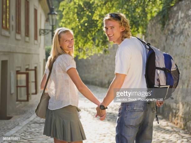 Caucasian couple holding hands on cobblestone street