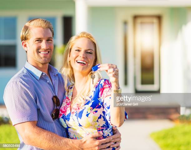 caucasian couple holding keys outside new home - cougar woman fotografías e imágenes de stock