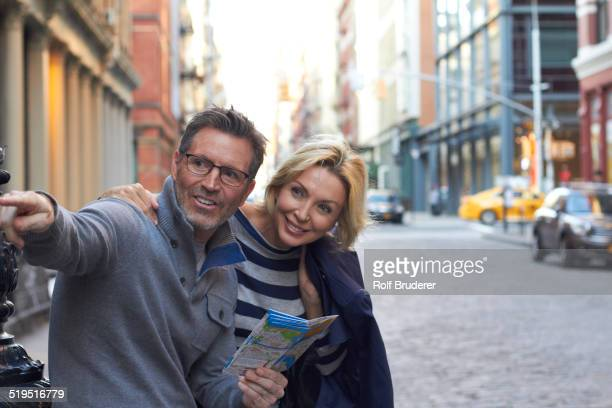 Caucasian couple holding map in city, New York City, New York, United States