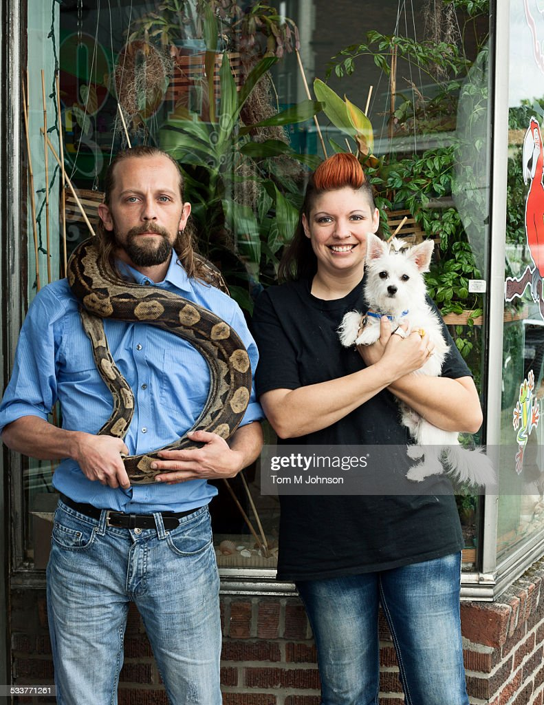 Caucasian couple holding pets outdoors : Foto stock