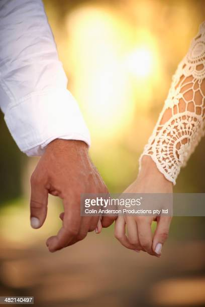 Caucasian couple holding pinkies in forest