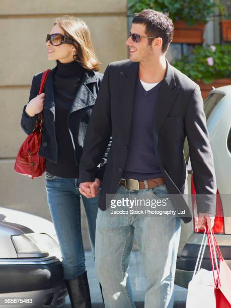 Caucasian couple holding shopping bags in city