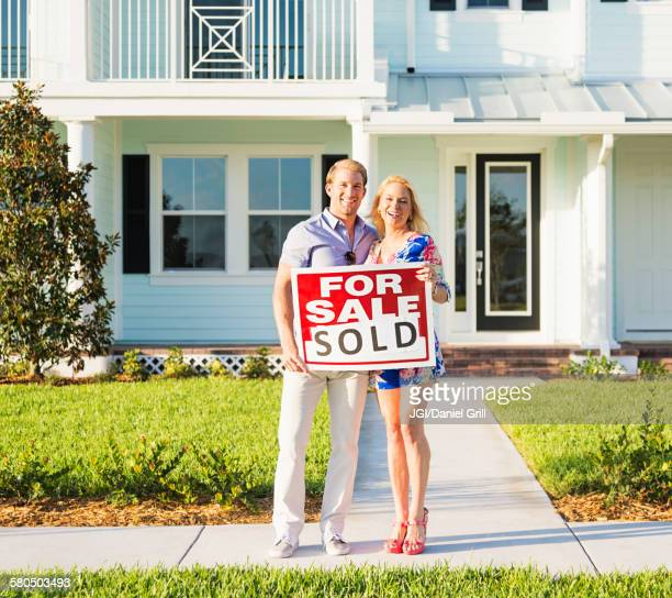 caucasian couple holding sold sign outside new home - cougar woman fotografías e imágenes de stock