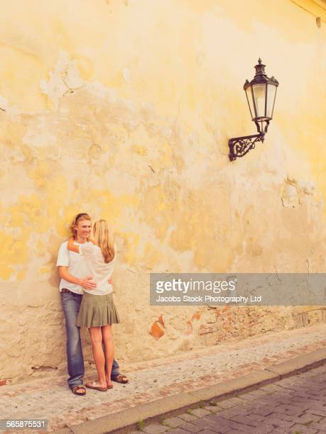 Caucasian couple hugging against dilapidated wall