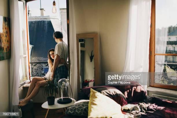 Caucasian couple hugging in apartment window