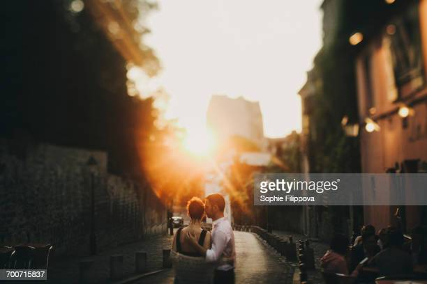 Caucasian couple hugging in city street at sunset