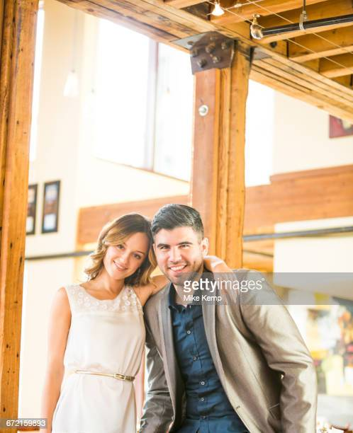 Caucasian couple hugging near beam