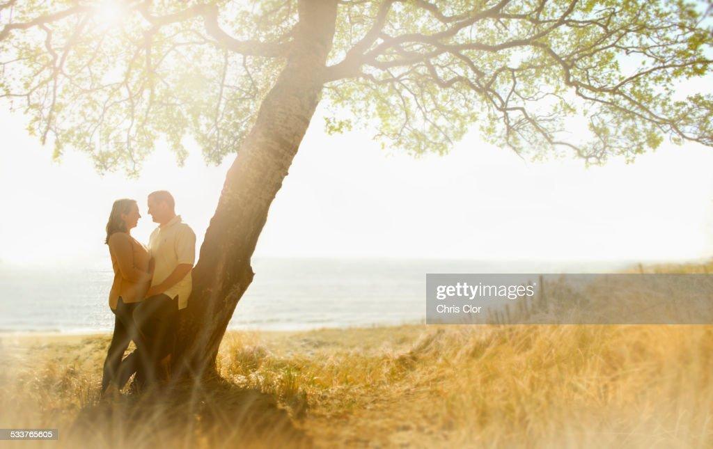 Caucasian couple hugging near tree in field : Foto stock