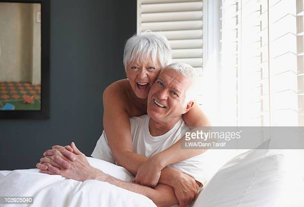 Caucasian couple hugging on bed
