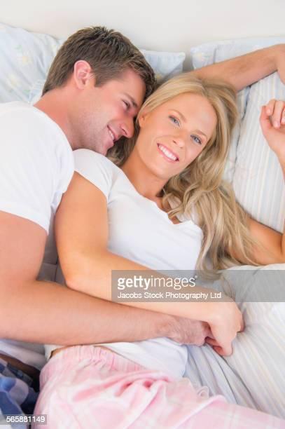 caucasian couple hugging on bed - abbracciarsi a letto foto e immagini stock