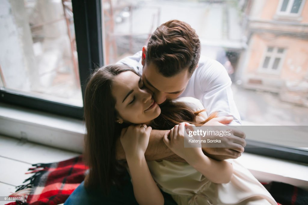 Caucasian couple hugging on bench near window : Stock-Foto