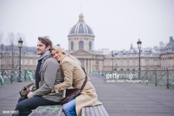 Caucasian couple hugging on bench, Paris, Ile-de-France, France