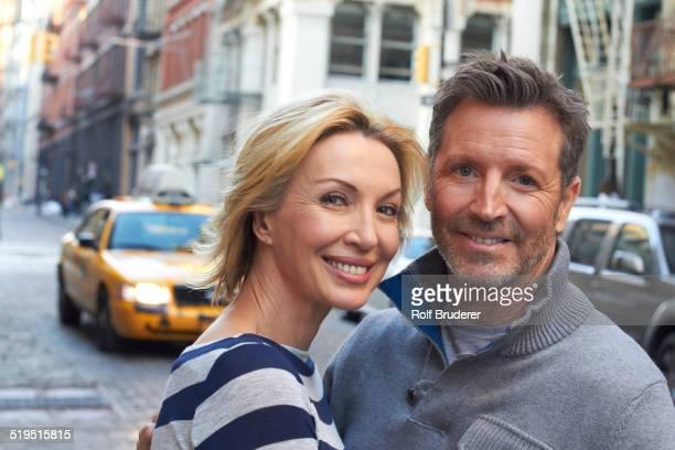 Caucasian couple hugging on city street, New York City, New York, United States