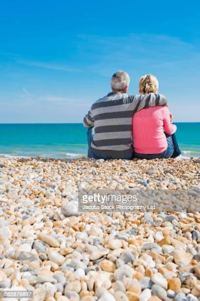 Caucasian couple hugging on rocky beach