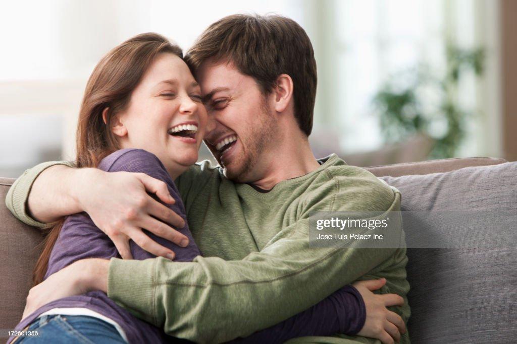 Caucasian couple hugging on sofa : Stock Photo