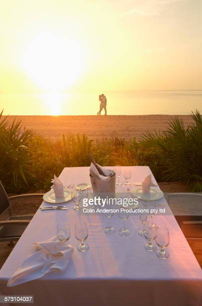 Caucasian couple hugging on sunset beach beyond dinner table