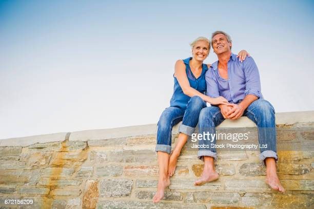 Caucasian couple hugging on wall at beach