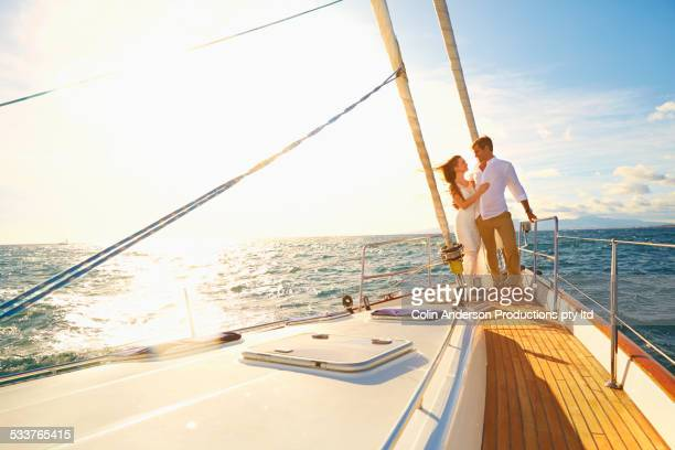 Caucasian couple hugging on yacht deck