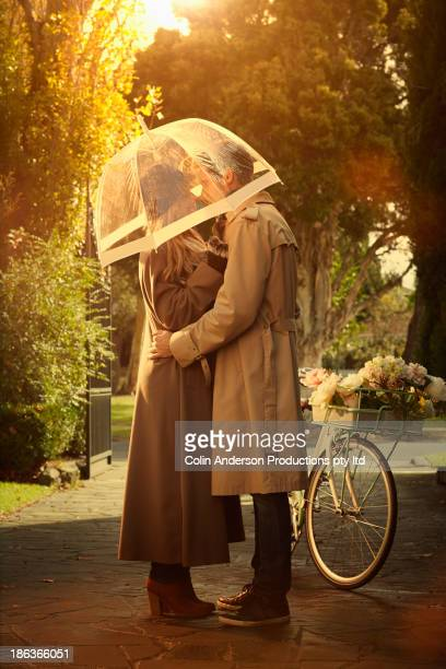 caucasian couple hugging under umbrella - couples kissing shower stock pictures, royalty-free photos & images