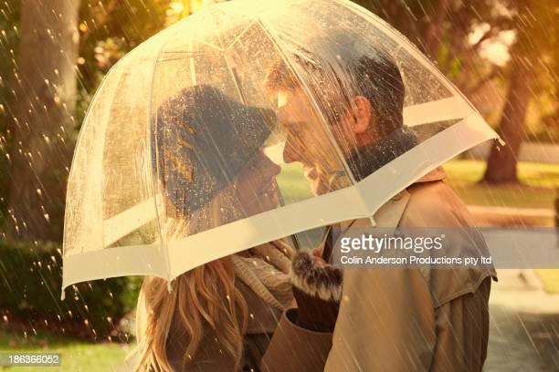 caucasian couple hugging under umbrella - romantic rainy day stock photos and pictures