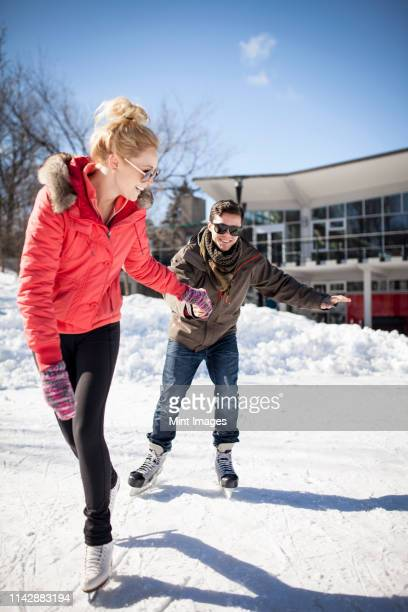 caucasian couple ice skating on frozen lake - showing respect stock pictures, royalty-free photos & images