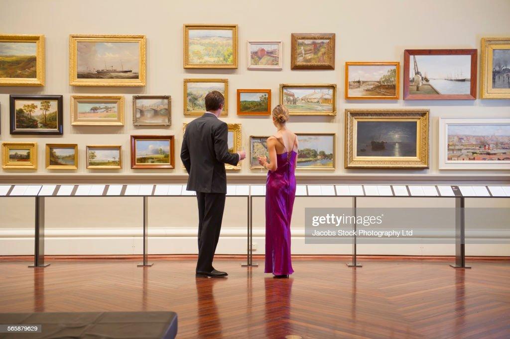 Caucasian couple in evening wear admiring art in museum : ストックフォト