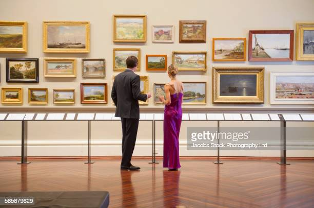 caucasian couple in evening wear admiring art in museum - konstmuseum bildbanksfoton och bilder
