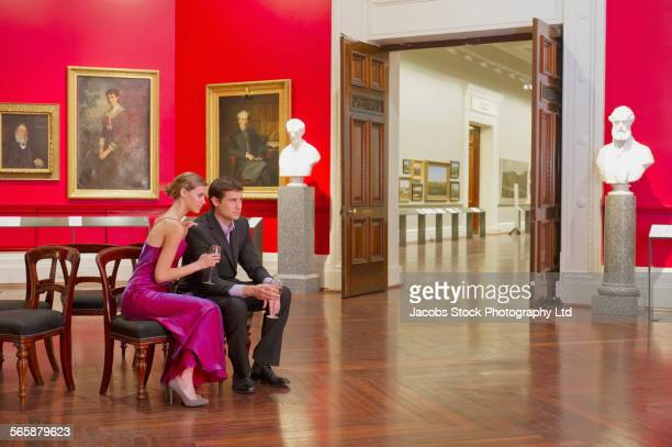 Caucasian couple in evening wear sitting in art museum