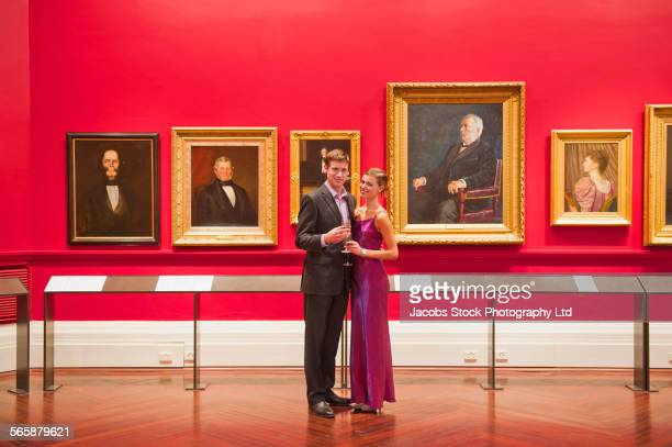 Caucasian couple in evening wear smiling in art museum