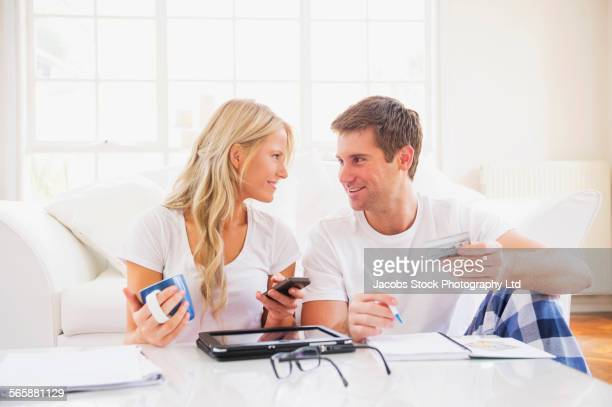 Caucasian couple in pajamas shopping online with digital tablet