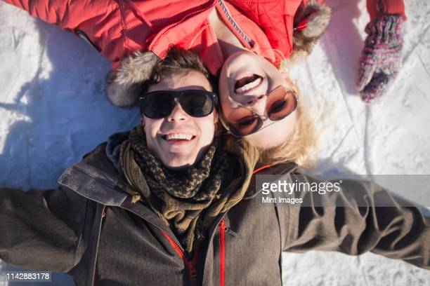 caucasian couple in sunglasses smiling in snow - canada stock pictures, royalty-free photos & images