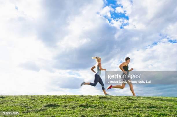 Caucasian couple jogging in grass field