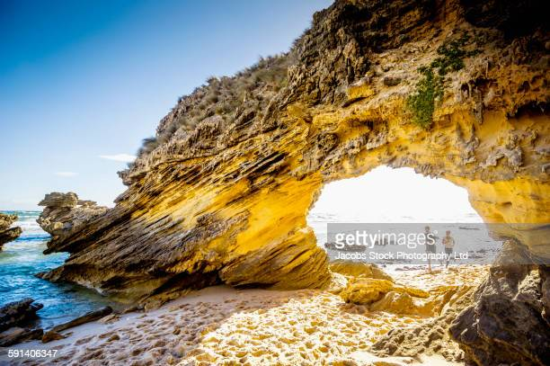 Caucasian couple jogging under rock formation on beach