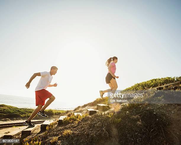 Caucasian couple jogging uphill