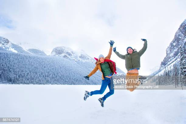 Caucasian couple jumping for joy near snowy mountains, Lake Louise, Alberta, Canada