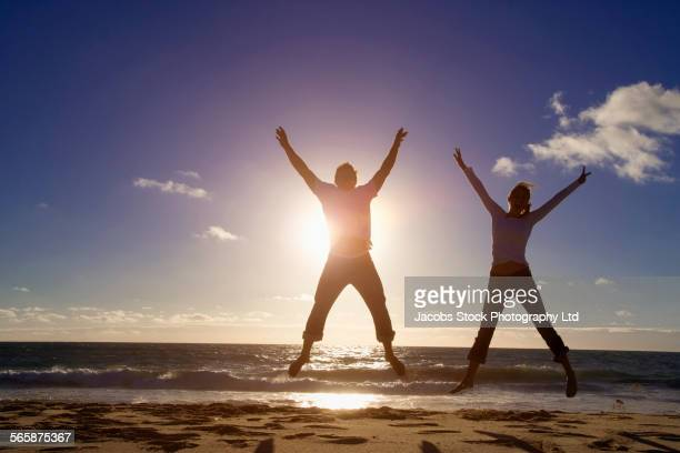Caucasian couple jumping for joy on beach