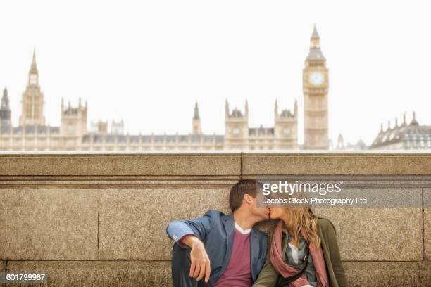 Caucasian couple kissing at clock tower, London, Middlesex, United Kingdom