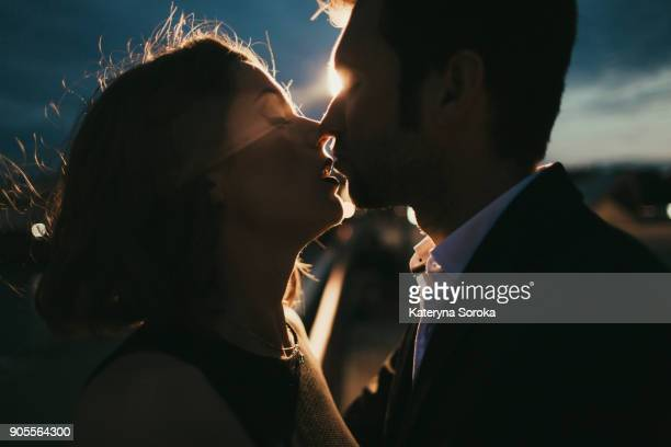 Caucasian couple kissing at night