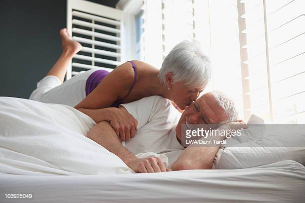 Caucasian couple kissing in bed