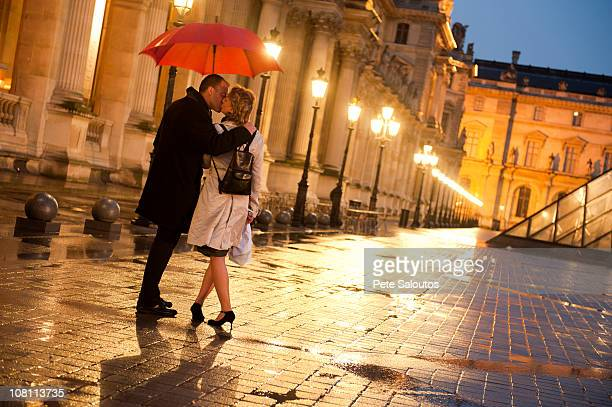 caucasian couple kissing in rain at night at the louvre - louvre photos et images de collection
