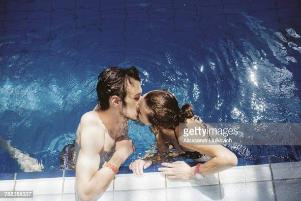 Caucasian couple kissing in swimming pool
