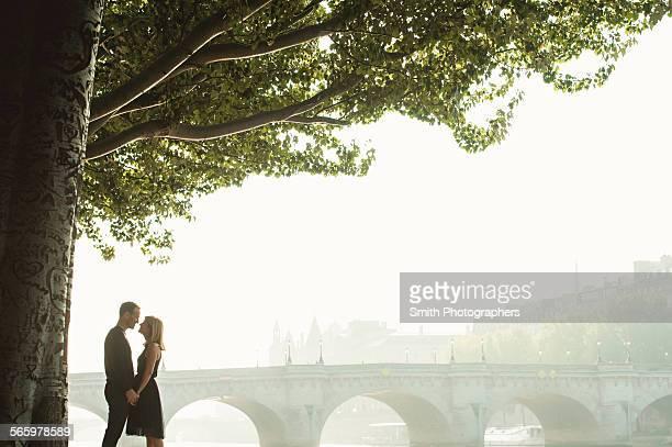 Caucasian couple kissing near bridge, Paris, Ile-de-France, France