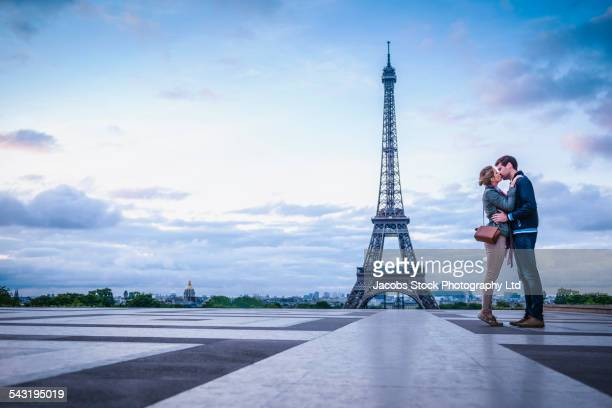 Caucasian couple kissing near Eiffel Tower, Paris, France
