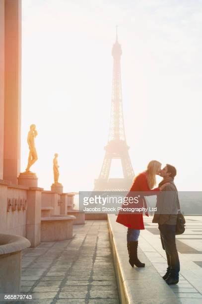 Caucasian couple kissing near Eiffel Tower, Paris, Ile-de-France, France