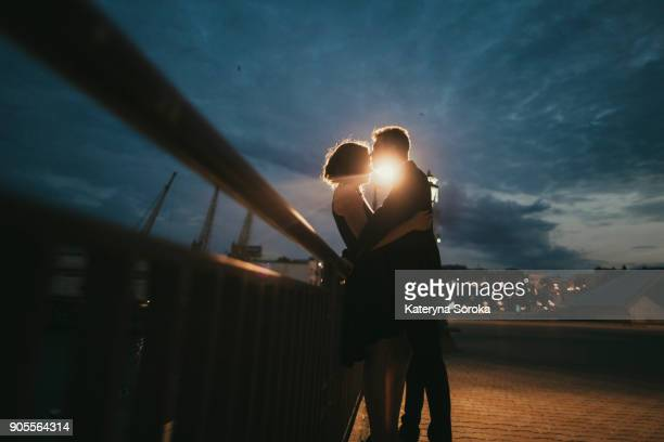 caucasian couple kissing near railing at night - romance fotografías e imágenes de stock