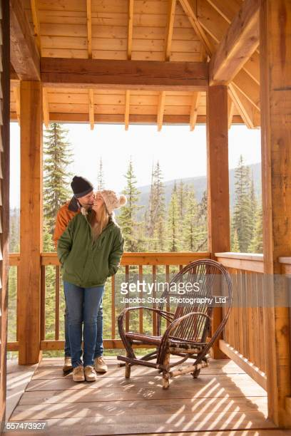 Caucasian couple kissing on log cabin porch